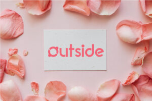 Outside logo on a card surrounded by pink flowers