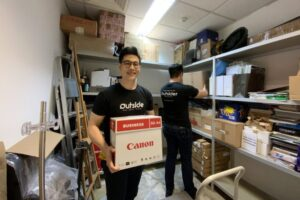 Two Outside team members clearing a storeroom